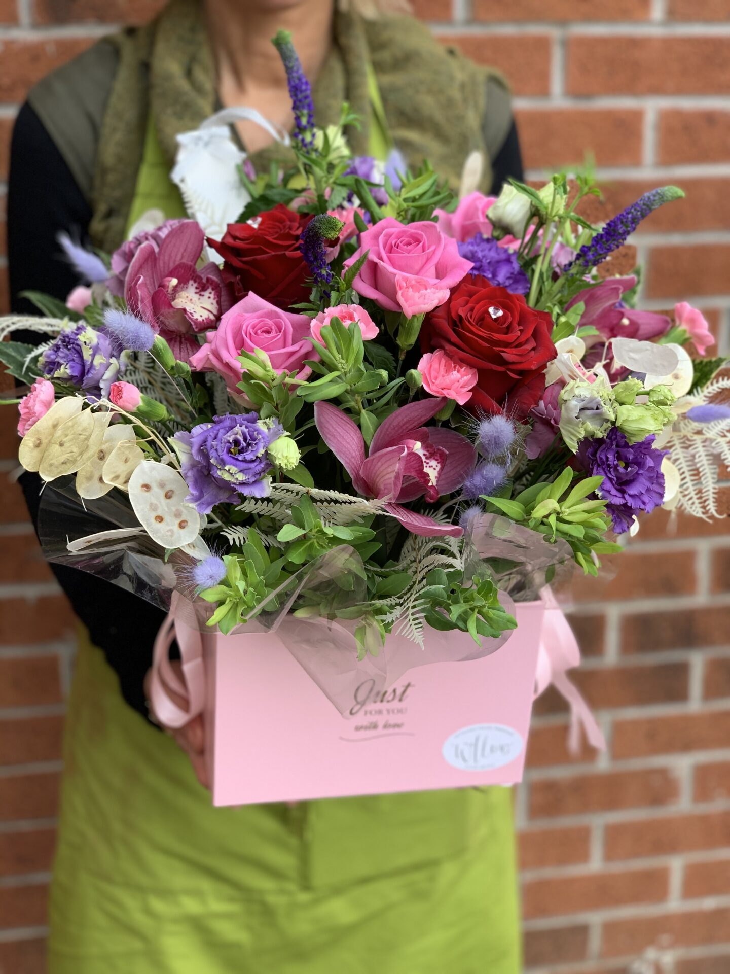 In this image, someone wearing a green apron is holding a bouquet in a bright pink box. The bouquet are a variety of pink flowers, some red flowers, some white flowers and even some deep purple ones.