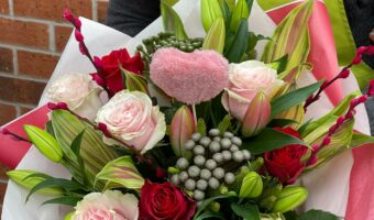 In this image, someone wearing a green apron is holding a bouquet. The bouquet is mainly pink with red and white flowers. There is also a pink heart in the middle