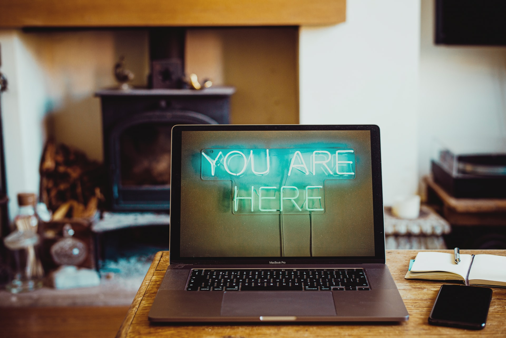 This image shows a laptop on a desk with a busy work space reading 'you are here' on the screen with LED effects.