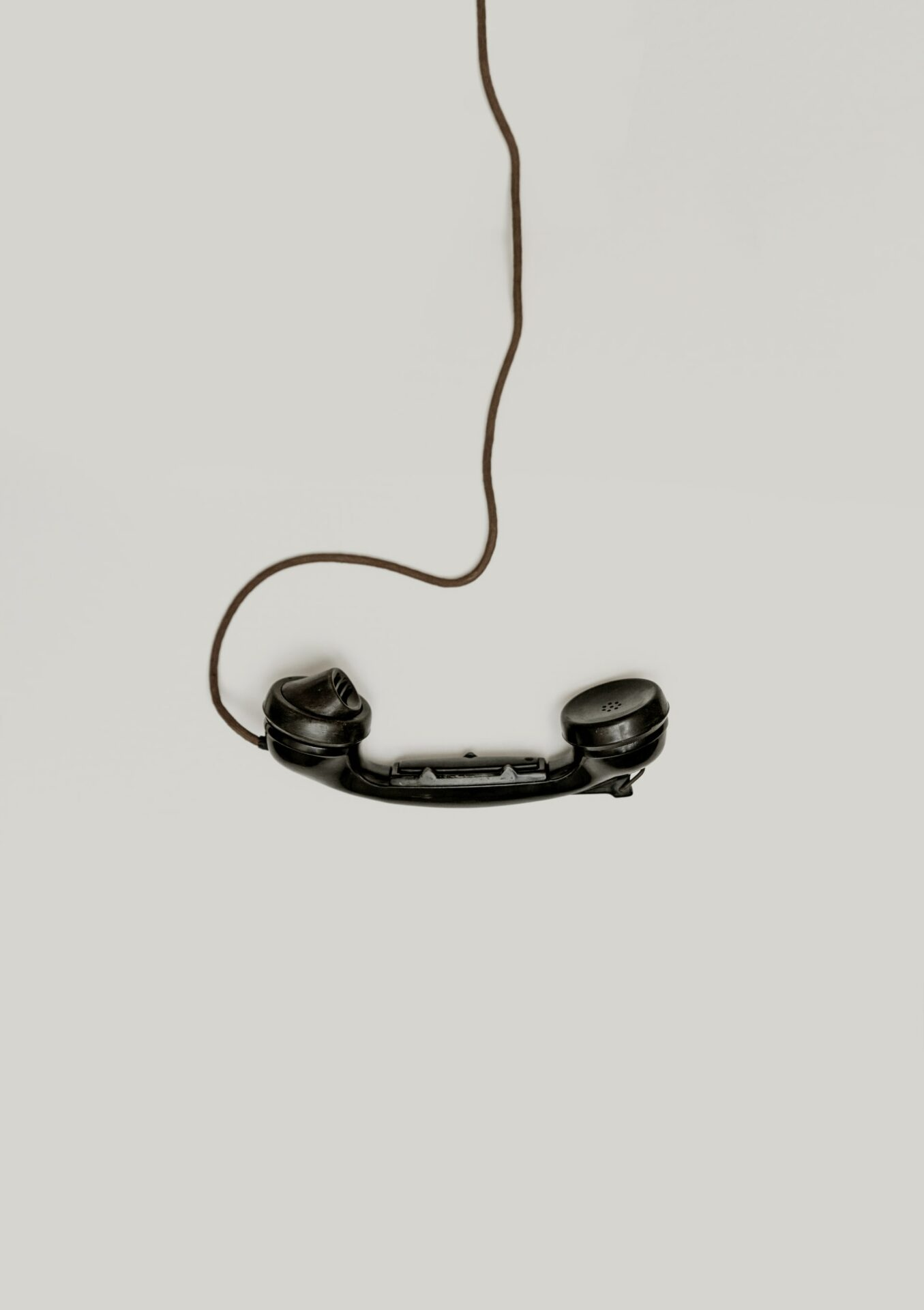 This image shows an old phone hanging from its cable.
