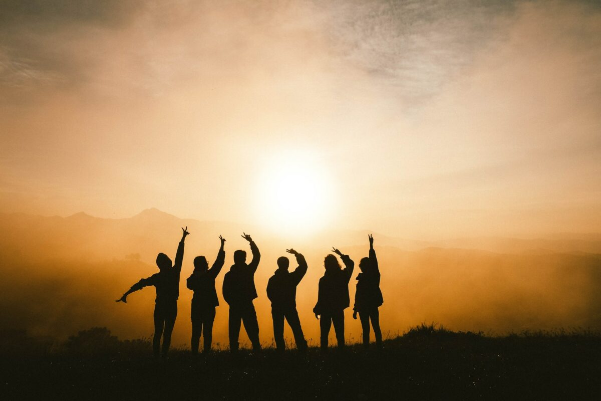 This image displays a group of friends standing in the sunset with their arms in the air.
