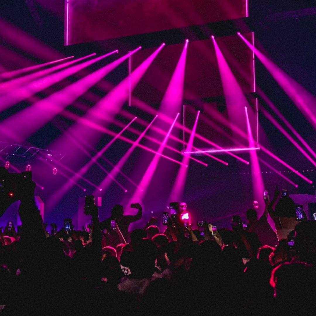 This image shows a nightclub filled with pink lighting and a huge crowd.