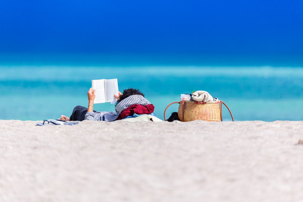 This images shows someone reading a book as they lounge on a sunny and sandy beach.