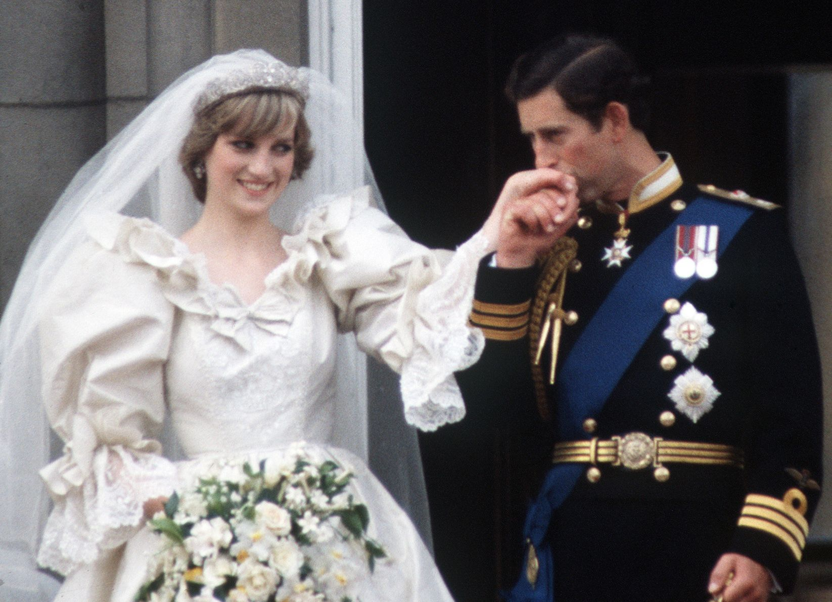 This image shows Prince Charles kissing Princess Diana's hand on the day of their wedding on the balcony of Buckingham Palace.