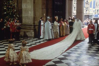 This image shows Princess Diana's iconic wedding dress with her long train following her out of the chapel.