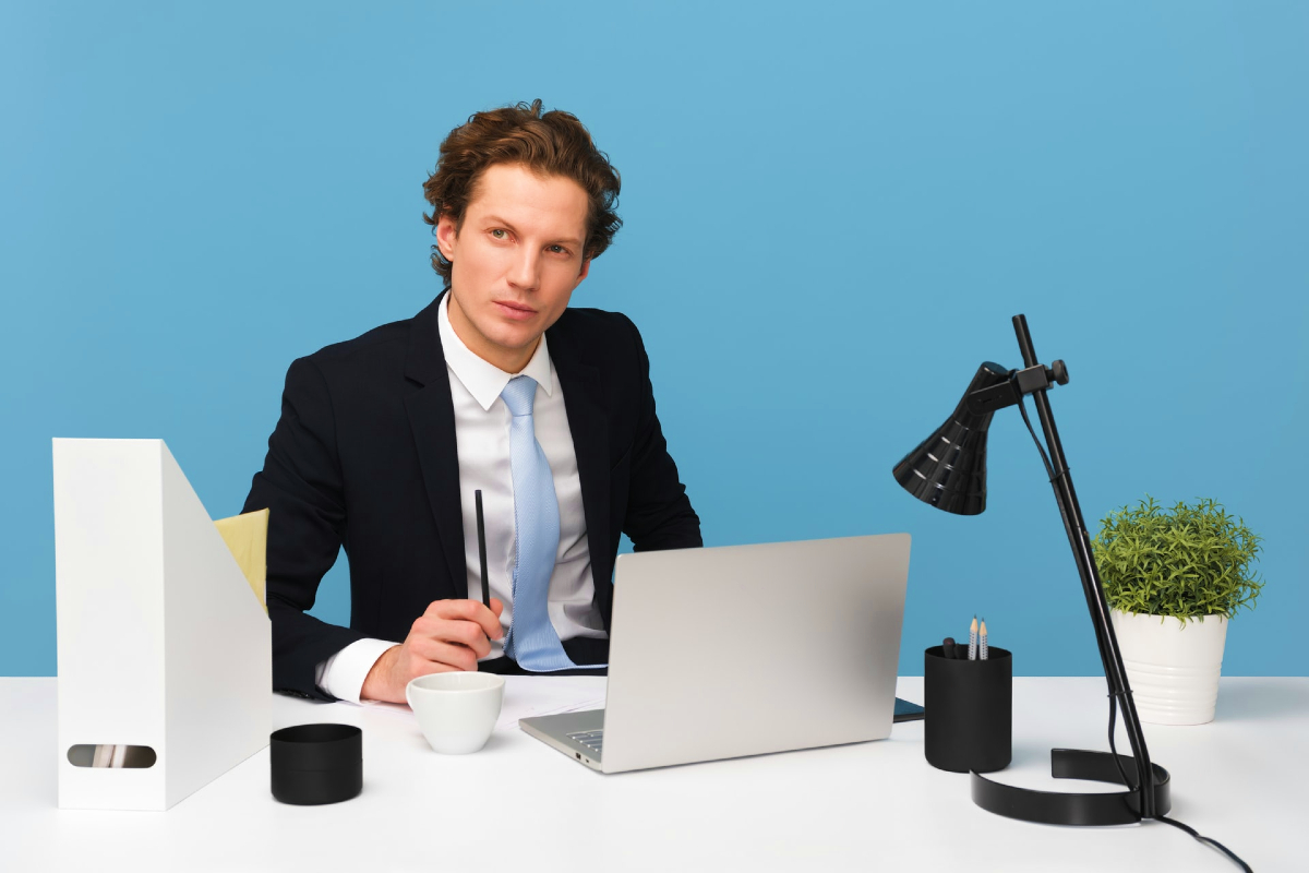 This image shows a man sitting at a desk with the bright blue tone of the photo as he stares into the camera.
