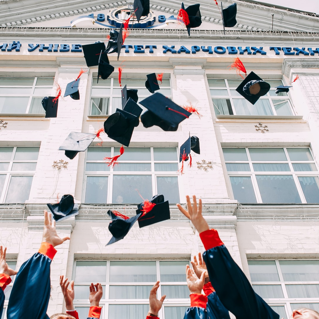 This image shows people throwing their graduation hats in the air.