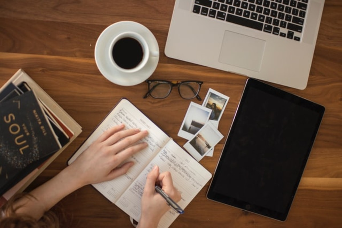 In this image, someone is writing in a notebook some polaroid pictures, a mug of coffee, a pair of glasses, a laptop and an iPad are surrounding them.