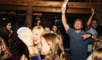 This image shows a basement house party with a group of girls in the foreground and a man jumping in the background.