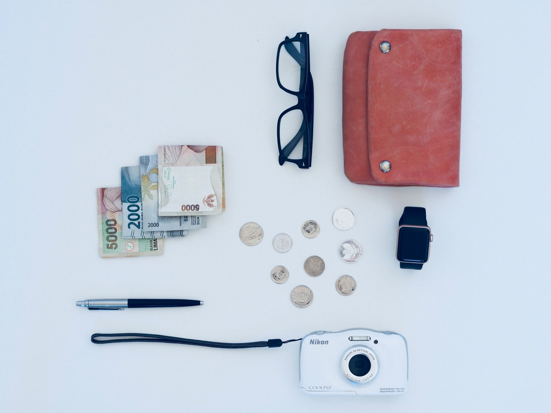 This image shows a white surface with a pair of glasses, money, a camera, coins, a watch, a purse and a pen on.