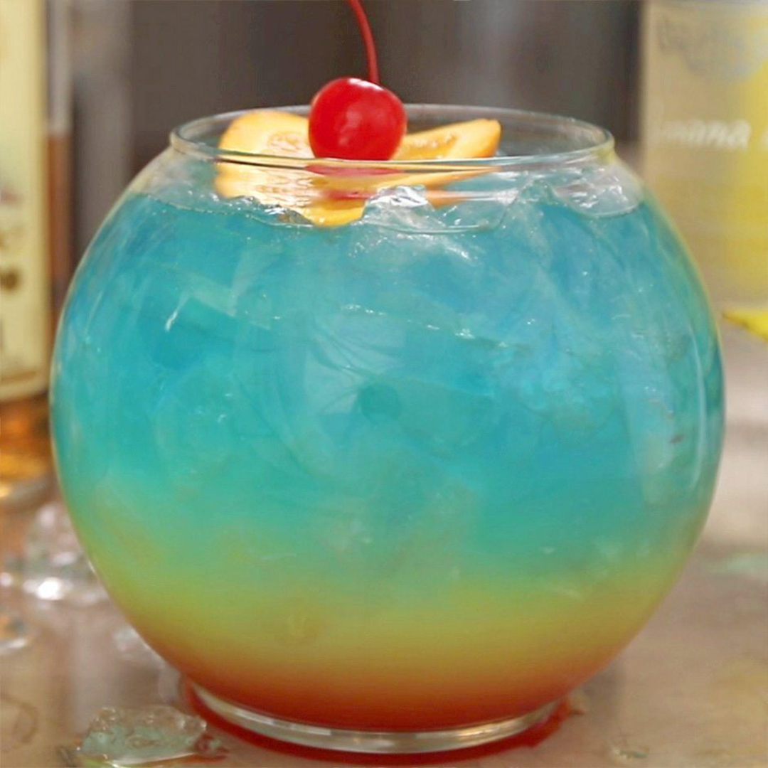 This is an image of a rainbow cocktail in a fish bowl.