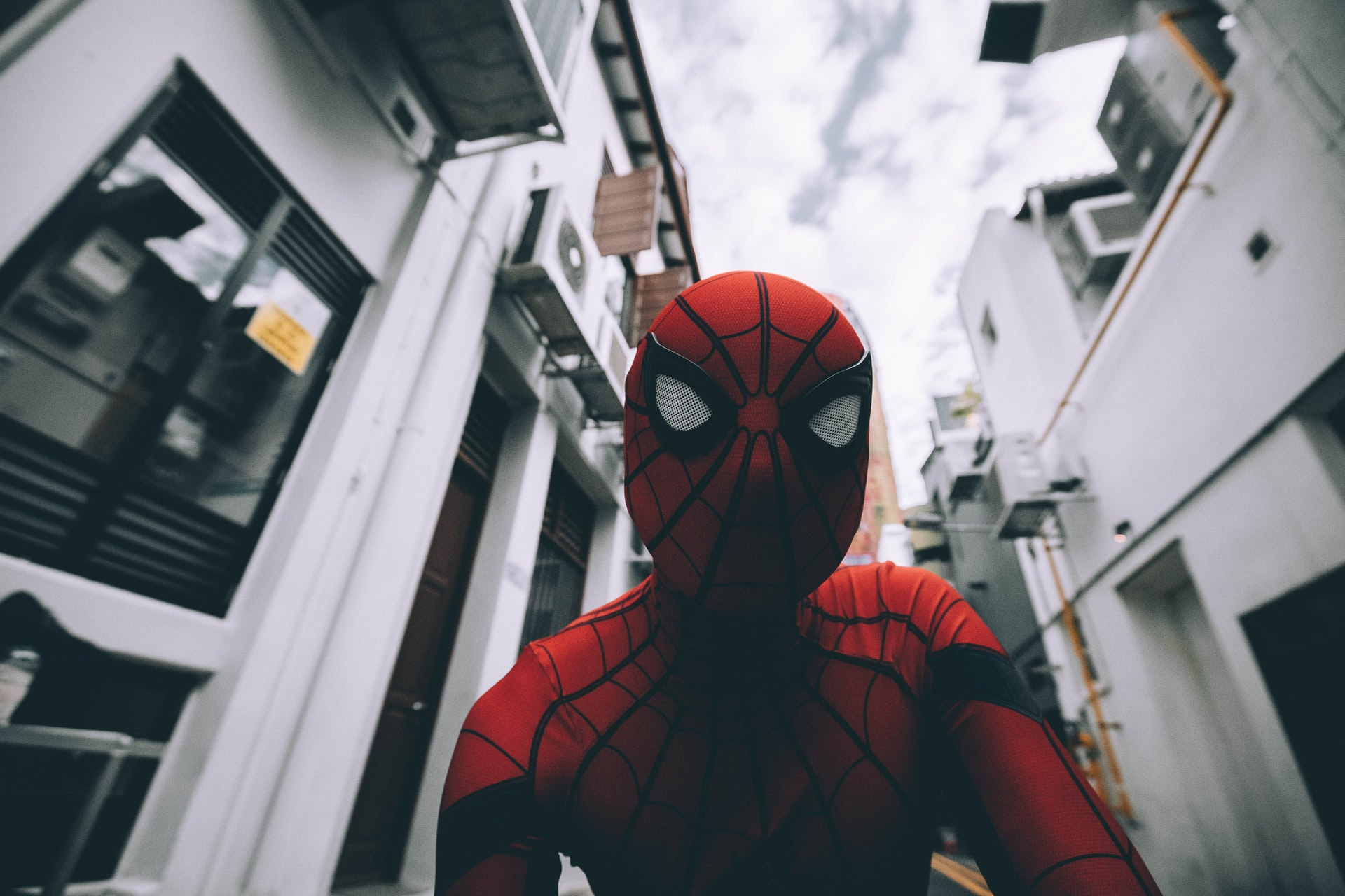 This image shows a person in fancy dress as Spiderman as the low angle photo looks up on buildings towering over the character.