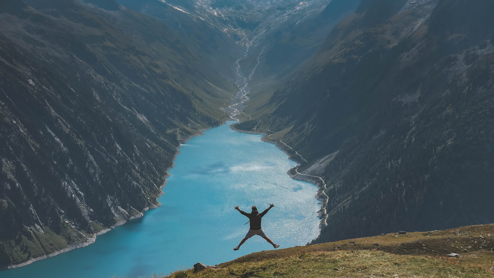 This image shows a man doing a star jump infront of a great lake.