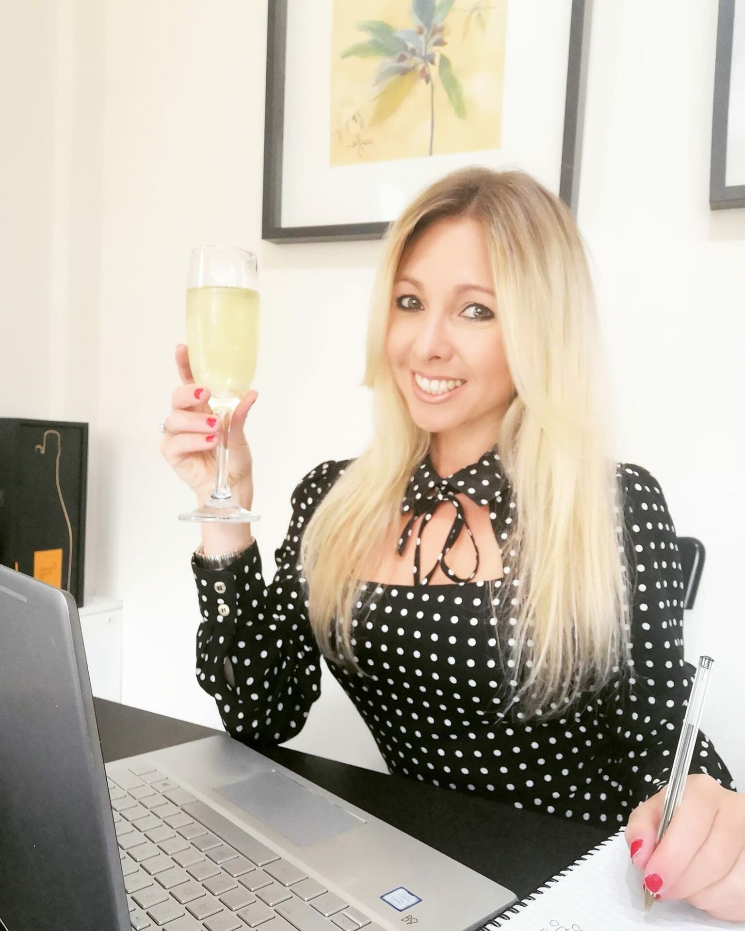 In this image, Laura is sat at a black desk with a laptop in front of her and writing on a notepad. In her right hand she is holding a glass of wine and is smiling at the camera.