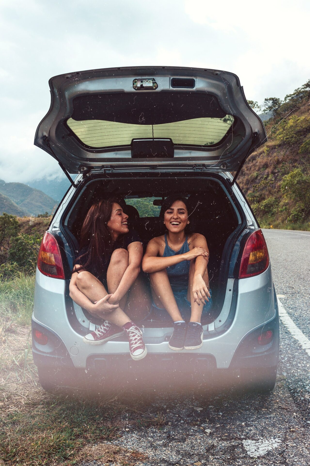 This image shows two young girls sitting in the boot of a car with the doors open as they laugh.