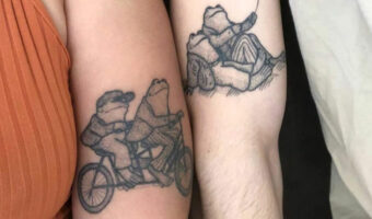 This image is a close up of two tattoos that match of frogs in black ink designed by tattoo artist, Jess Oxley.