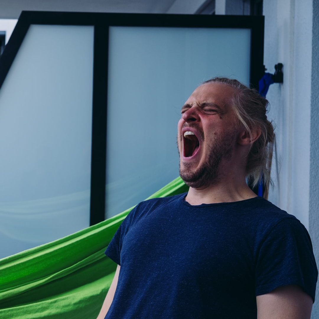 This image shows a man sitting on a hammock yawning.