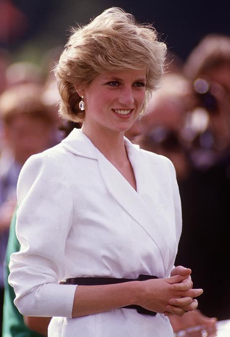 Diana is pictured here wearing a white blazer dress smiling. In the background is crowds of people.