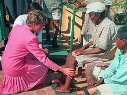 This image shows Princess Diana wearing all pink during her Leprosy Mission as she touches the leg of a patient.