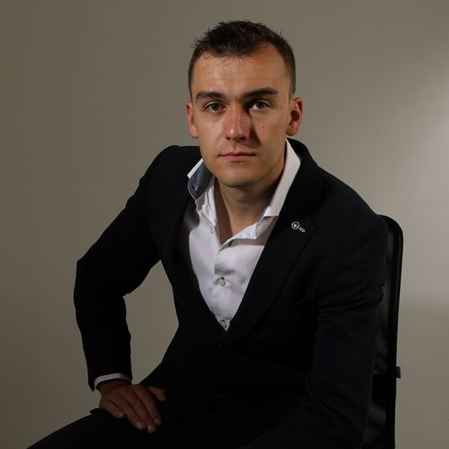 This image shows Joe Maw looking directly at the camera with a straight face. He is wearing a suit with his top buttons undone.