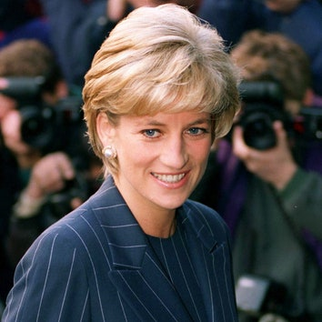 This image shows a background of paparazzi with a smiling Diana in the foreground wearing a blue blazer.