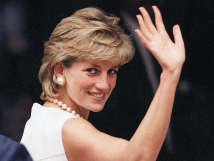 This image shows an over the shoulder look from Diana as she waves to the crowds as she wears a white dress complimented by her pearl necklace.