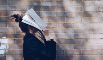 In this image, someone is standing next to a grey, brick wall and they are holding a book over their face.