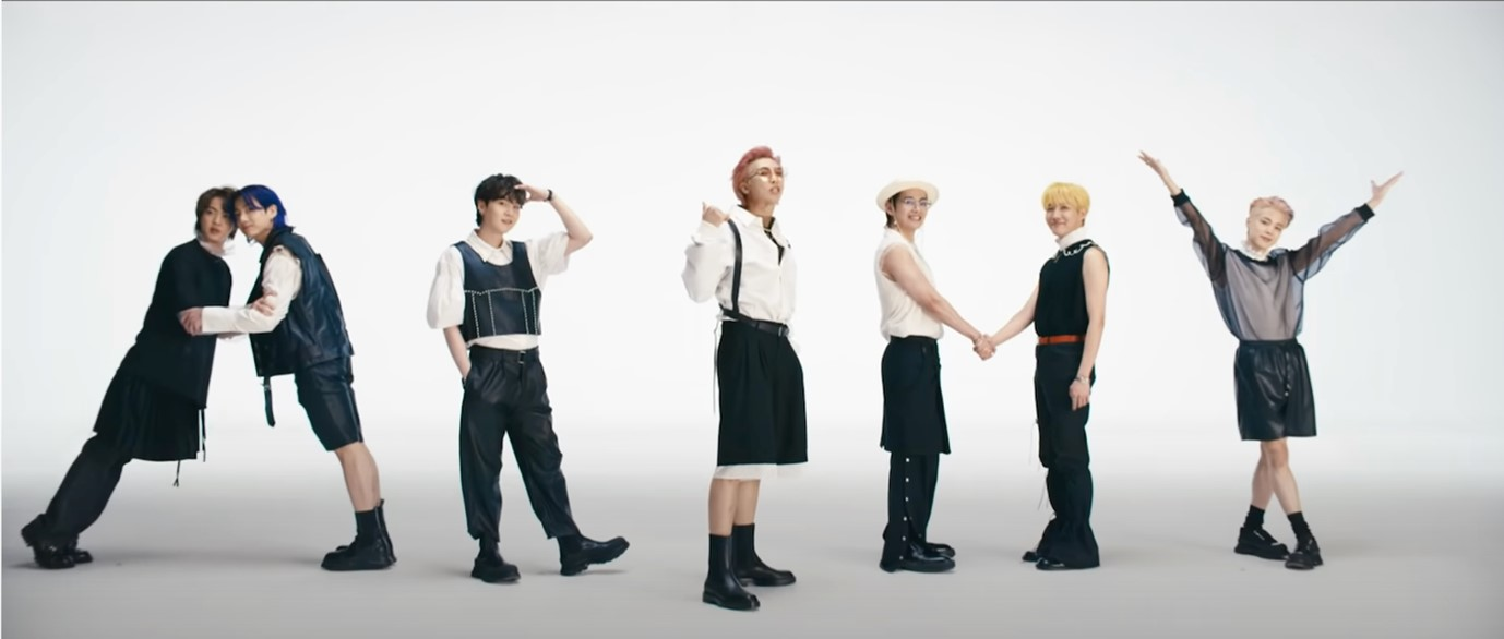 """In this image, the BTS boys are dressed in different outfits, but the outfits are all black and white. The boys use their bodies to spell """"ARMY"""", the name of their fandom."""