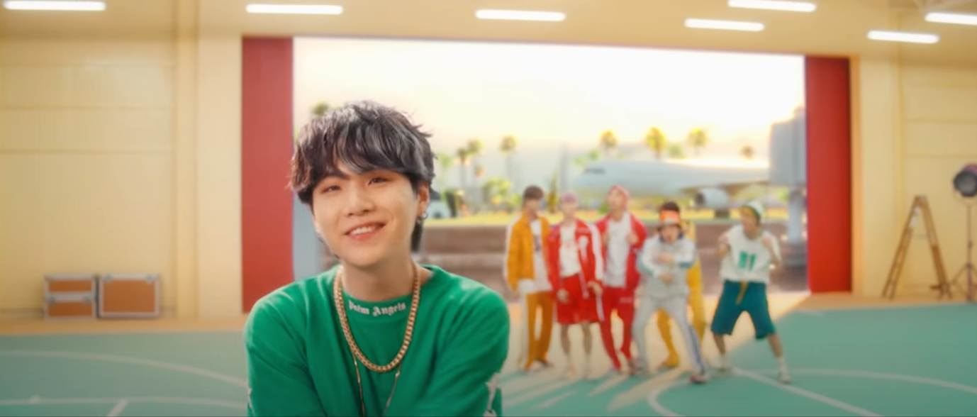 In this image, Suga is rapping directly to the camera. He is wearing a green, sporty top with a gold chain. Behind him, to his left, the rest of the boys are casually dancing to his rap. Behind all of them is a green screen showing palm trees and a plane.