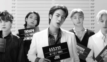 In this image, BTS are lined up against a wall height chart. The image has been edited to look black and white. They are all in suits and expensive clothing. They are holding boards that have their names and a number on, those you see criminals holding when their prison photos are taken.