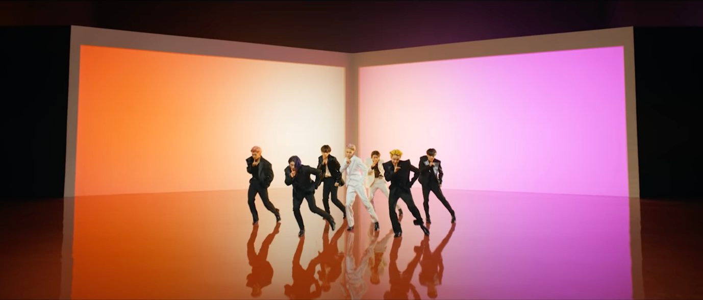 In this image, BTS are dancing in front of two large, lit-up screens. One is orange and the other is pink.