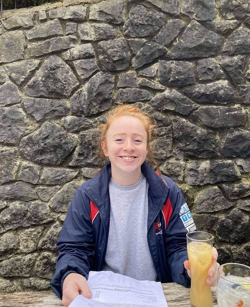 This image shows Catherine sat at a table outside. In front of her is a drink and some papers. Behind her  is a grey stone wall.