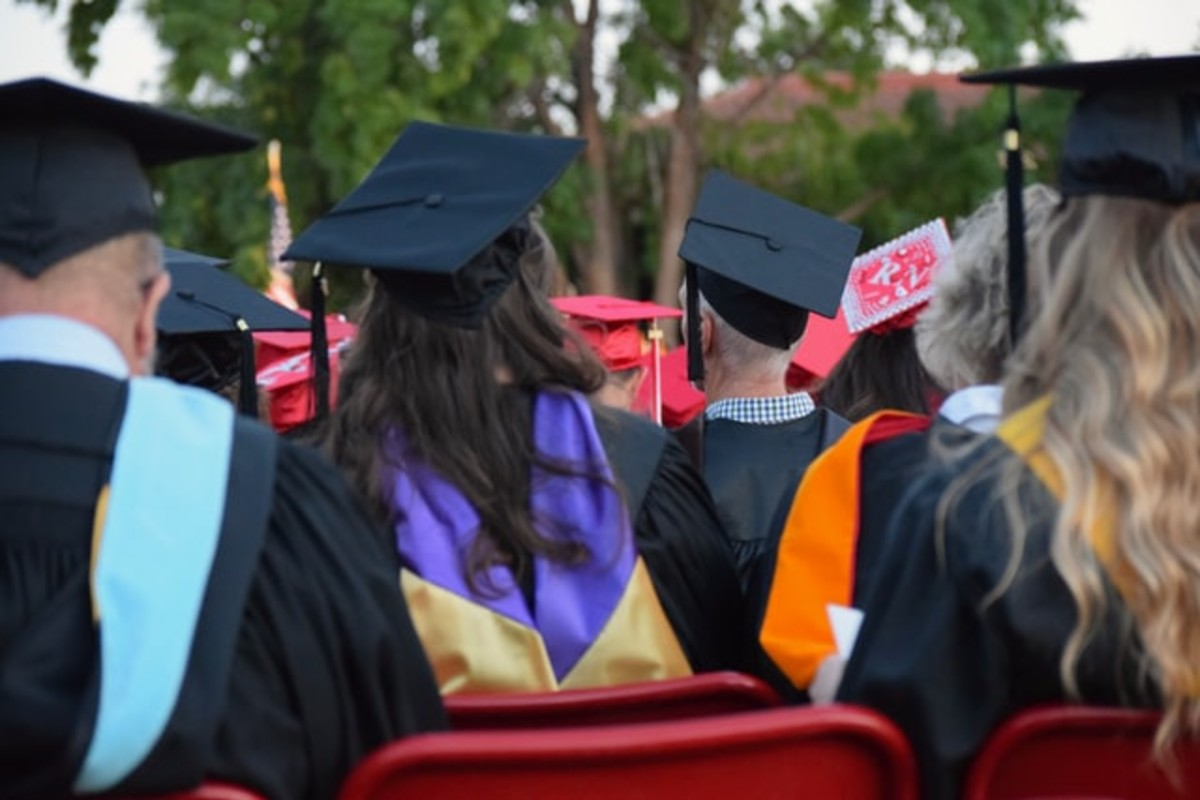 In this image, people are sat down during their graduation. The picture has been taken from behind the audience, so you can see the graduation caps they are wearing.