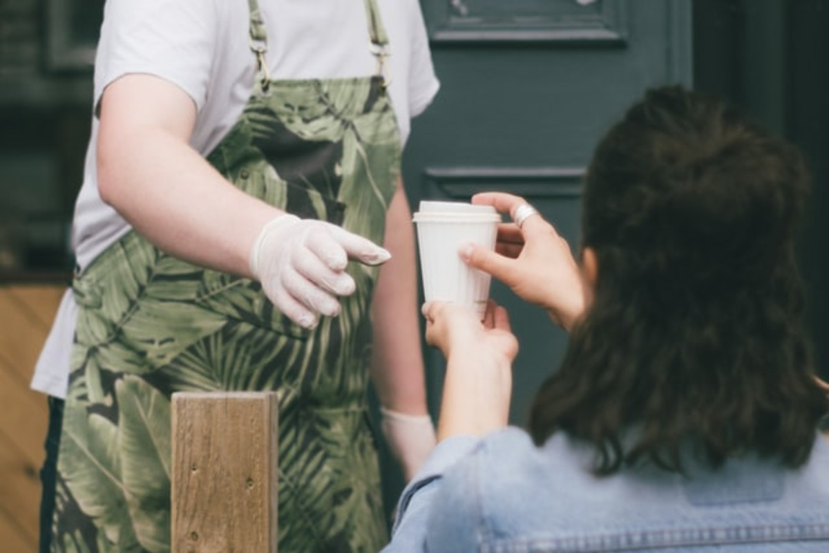 In this image, someone earing a blue denim jacket is passing a takeaway cup to someone wearing a white top, white gloves and a palm leaf print apron.