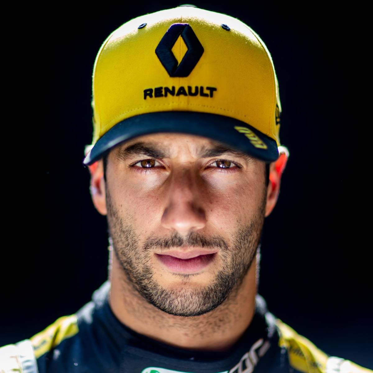 This is an image of Daniel Riccardo, he is an F1 driver. He is looking directly into the camera with a serious facial expression. He is also wearing a black and yellow baseball cap, which has RENAULT written on it and the company's logo above.