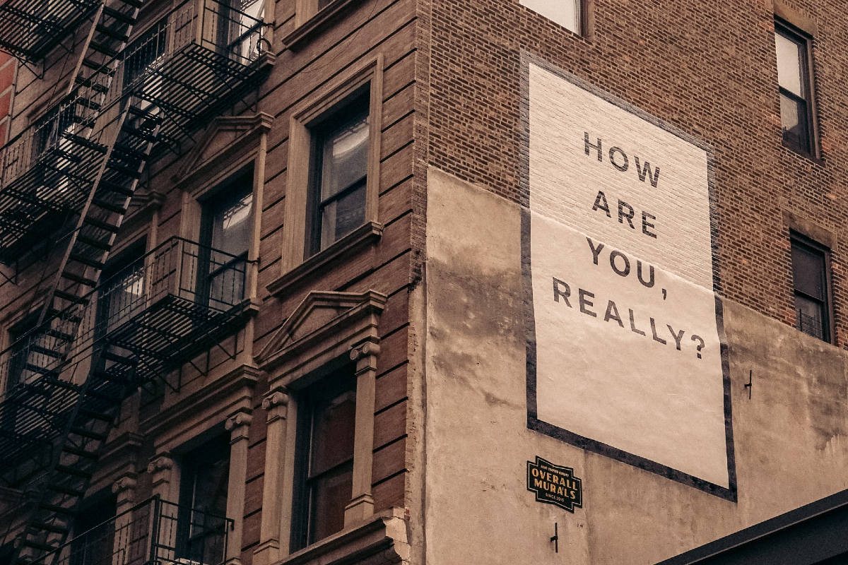 This image shows the outside of a building with a sign reading 'how are you really?