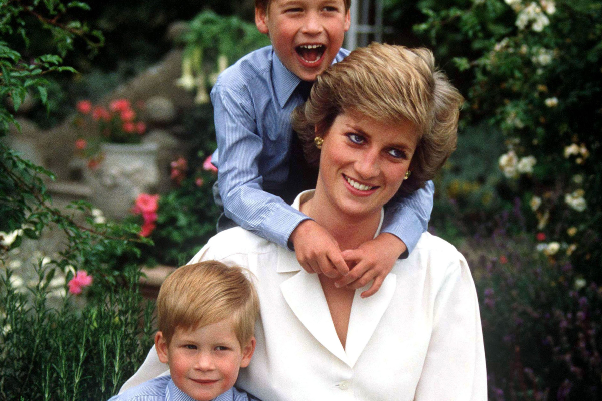 This image shows Diana with a young Harry sitting on her lap and William on her back with his arms wrapped around her mum as the three smile candidly.