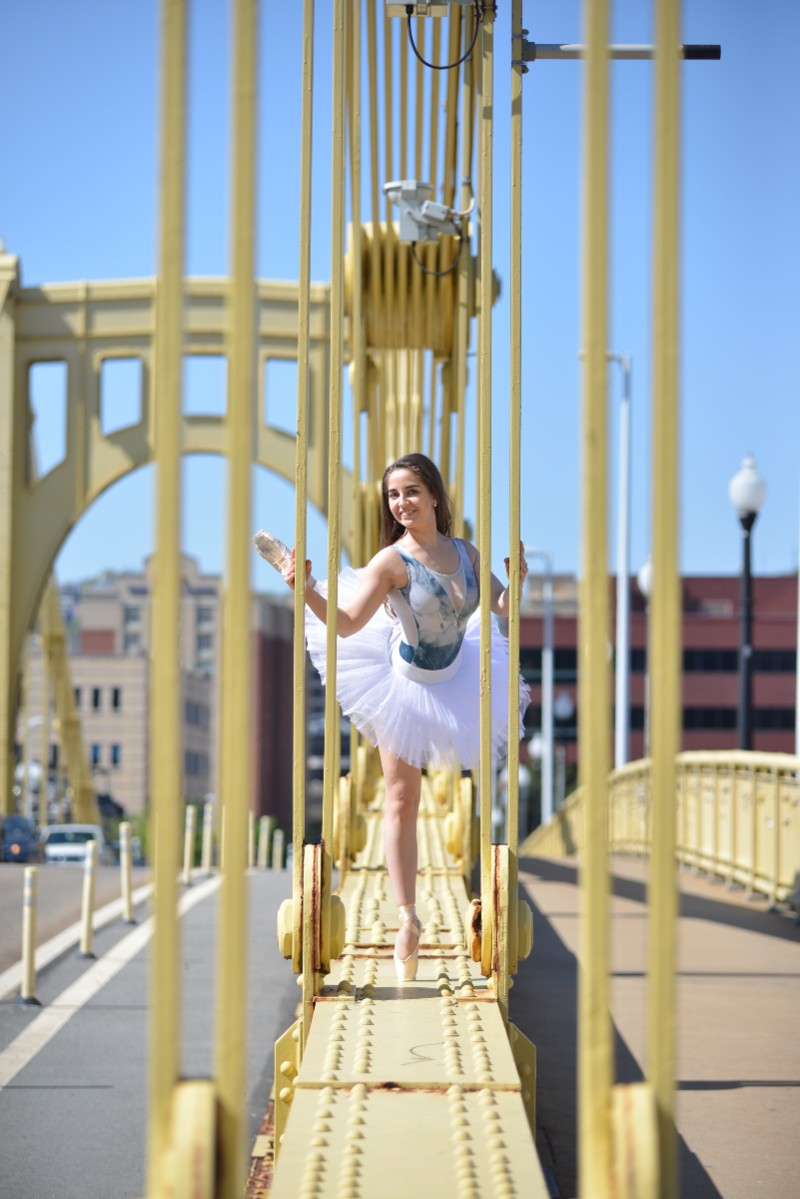 In the image, Katja is wearing a ballet outfit and dancing between poles on a yellow bridge.