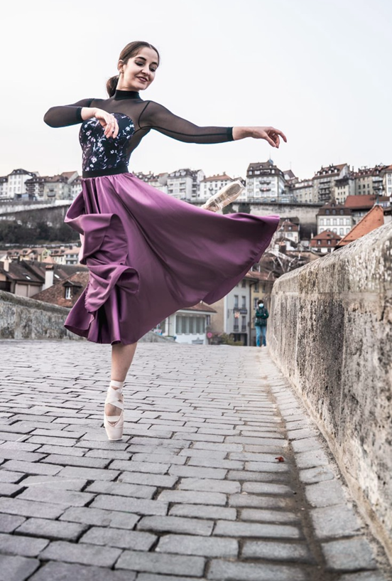 In this image, Katja is wearing a black top with a purple skirt and ballet shows. She has one leg in the air and her top half of her body is turned to face behind her. She is dancing on a stone bridge.