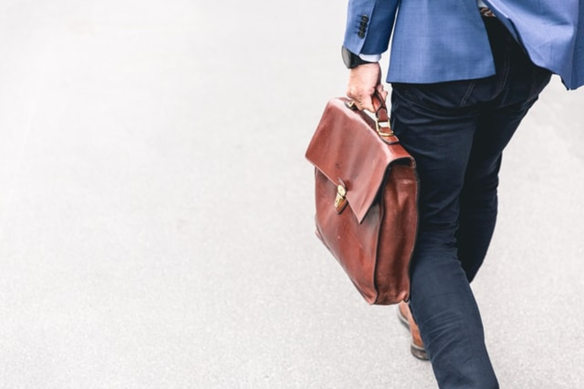 In this image, a man is wearing smart office-wear clothing and carrying a brown, leather workbag.