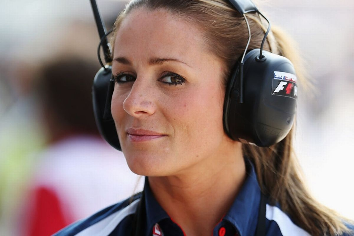 This is an image of Natalie Pinkham. She is wearing a headset, which is black, and a blue, red, and white jacket.