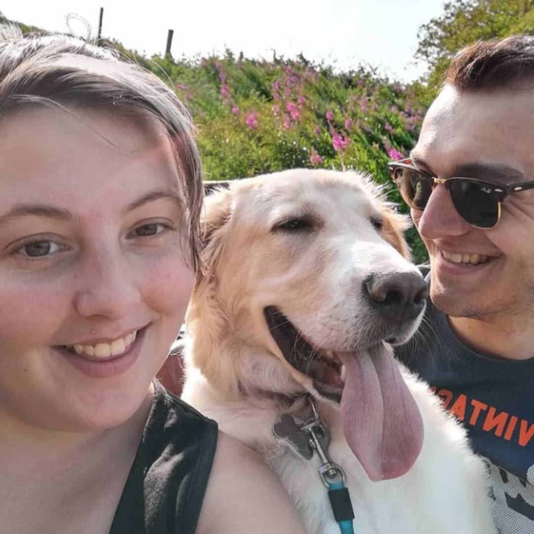 This image shows actor Joe Maw with his fiance, Courtney Richardson and their dog Ryder in the middle with his tongue out.