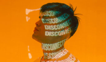 This image shows a man standing side on with a screen reflecting off his face reading 'disconnected'. Behind him is a bright orange board.