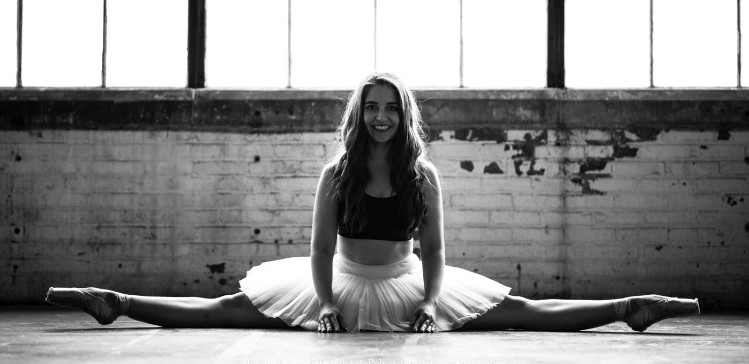 In this image, Katja is wearing a black crop top and a white ballet skirt, along with ballet shoes. She is doing the splits. The image has a black and white effect on it.