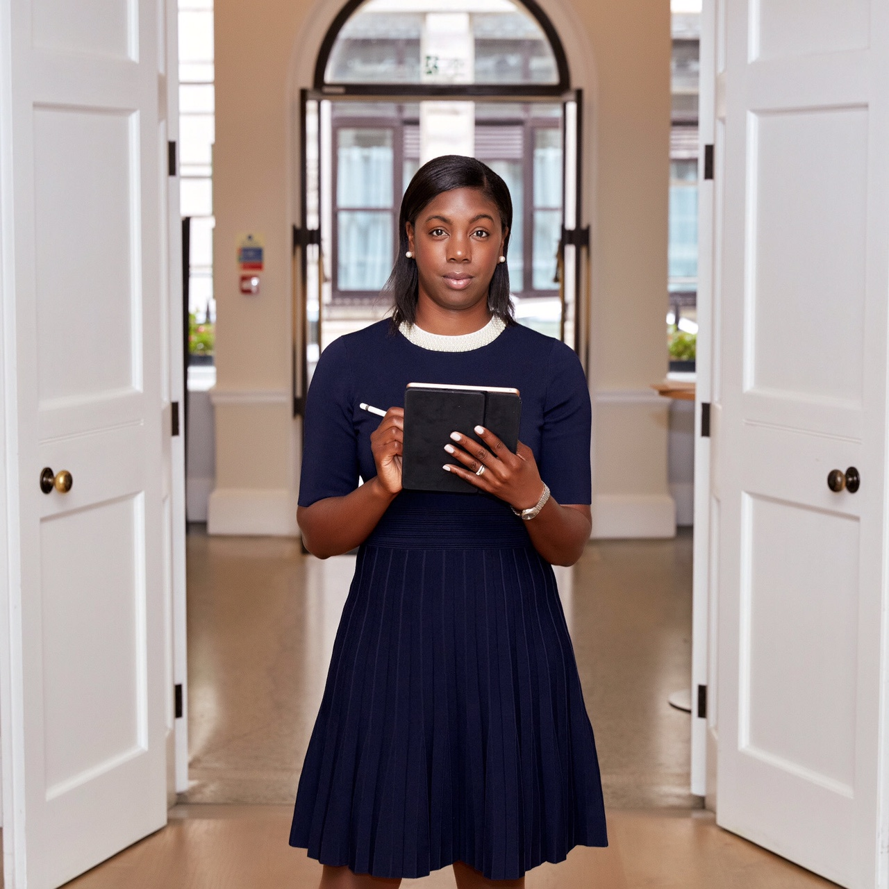 In this image, Marsha is facing the camera, stood up. She is stood in front of two large, white doors that are open to show the front of the building. Marsha is wearing a navy dress that has a white collar. Marsha is looking directly at the camera. In her hands is a pen and notepad.