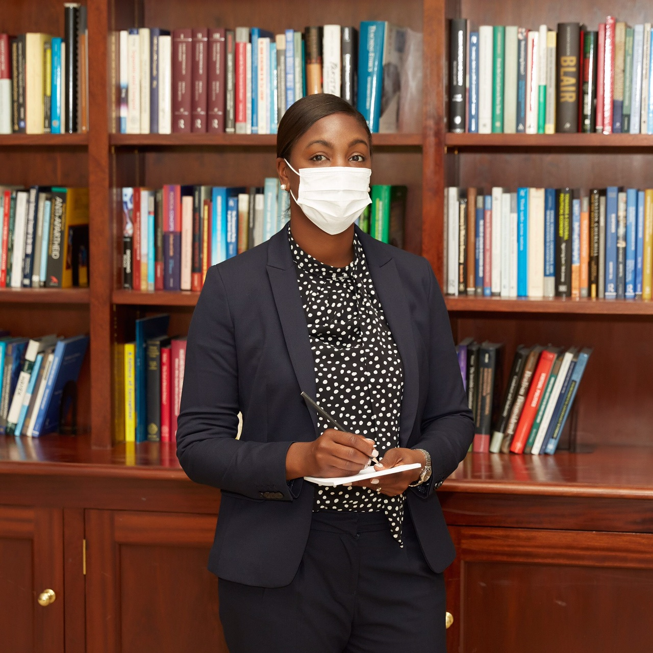 In this image, Marsha is wearing a dark suit and a white polka dot blouse. In her hands is a pen and notepad. Marsha is wearing a white face mask. Behind her is a bookcase, full of books.