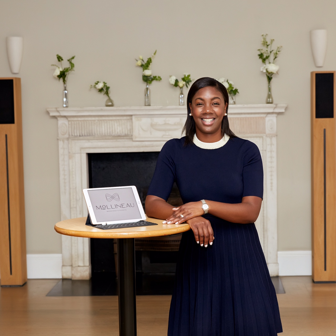 This image shows Marsha, dressed in a navy blue dress with a white collar, leaning against a table. On top of the table is an iPad which shows her business's logo on the screen. Behind her is a white, elegant fireplace that is decorated with white flowers.