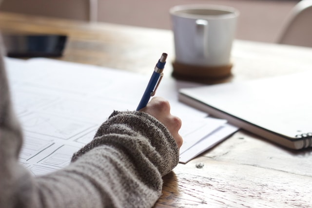 In this image, someone is working/writing at a table. On the table are some notebooks and multiple sheets of paper. Also on the table is a white mug.