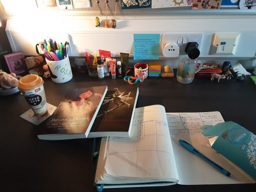 In this image, the table is a darker colour. On top of the table are a few books, one of them is open and the others are scattered around it. Also on the table is a pen pot, a few skin care products, a drink and a few stationary pieces. On the wall above the table is a couple of plug sockets.