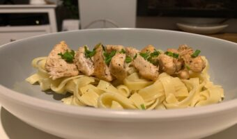 This image shows a bowl of tagliatelle pasta with a layer of chicken on the top, garnished with chives.